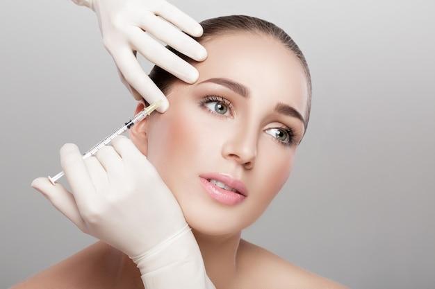 Portret van mooie vrouw die injectie krijgt. schoonheidsinjecties en cosmetologie