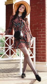 Portret van mooie vrouw die jurk en strohoed draagt op zonnige warme weerdag. wandelen in het zomerpark.