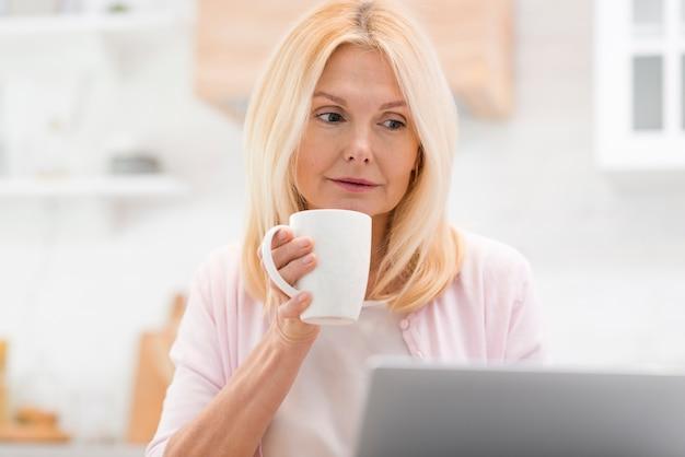 Portret van mooie vrouw die laptop bekijkt
