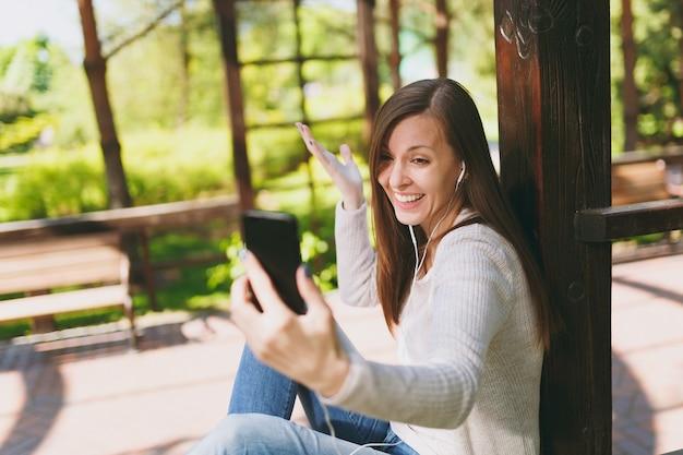 Portret van mooie vrouw die lichte vrijetijdskleding draagt. lachende vrouw zittend in stadspark in straat buiten op lente natuur, selfie schot op mobiele telefoon of video-oproep doen. levensstijlconcept.