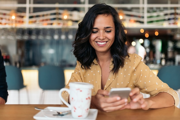 Portret van mooie vrouw die mobiel in coffeeshop gebruikt.