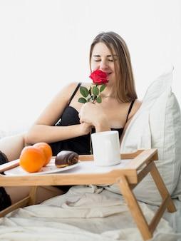 Portret van mooie vrouw die ontbijt op bed heeft en rode roos ruikt