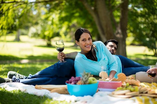 Portret van mooie vrouw die op picknickdeken leunen