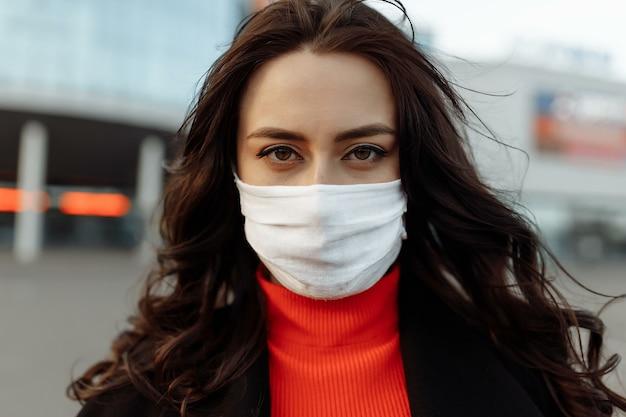 Portret van mooie vrouw die op straat loopt die beschermend masker draagt als bescherming tegen infectieziekten. aantrekkelijk ongelukkig model met griep buitenshuis.