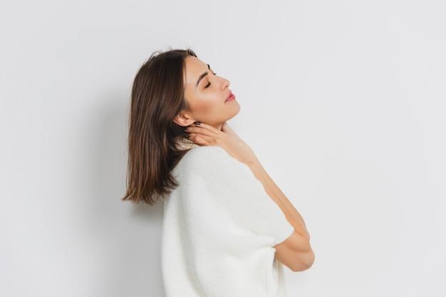 Portret van mooie vrouw die op witte studio wordt geïsoleerd