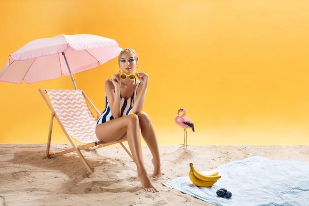 Portret van mooie vrouw die op zonnebril op de zomerdecor zet