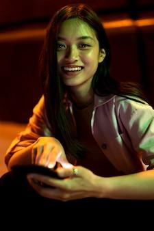 Portret van mooie vrouw die 's nachts smartphone gebruikt in de stadslichten
