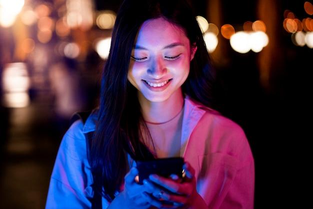 Portret van mooie vrouw die 's nachts smartphone gebruikt in de stadslichten Gratis Foto