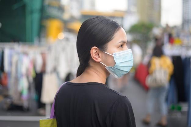 Portret van mooie vrouw draagt gezichtsmasker in winkelcentrum