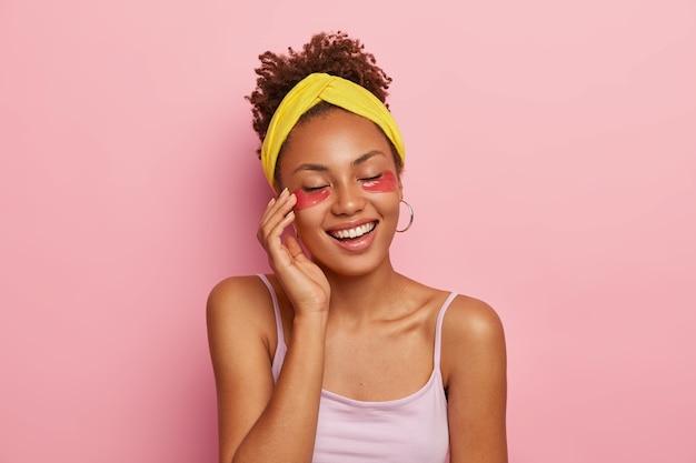 Portret van mooie vrouw draagt ooglapjes, geniet van het effect van een perfecte huid, houdt de ogen gesloten, draagt een gele hoofdband en een casual t-shirt