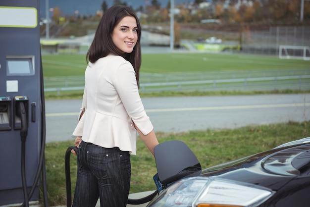 Portret van mooie vrouw elektrische auto opladen