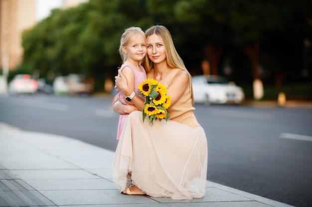 Portret van mooie vrouw en meisje met zonnebloemen