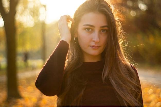 Portret van mooie vrouw en weg kijken naar park tijdens zonsondergang