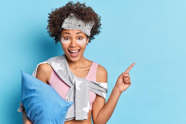 Portret van mooie vrouw geeft op kopie ruimte gekleed in pyjama kostuum houdt zacht kussen heeft gelukkige uitdrukking geïsoleerd over blauwe muur draagt slaapmasker. je promo is hier.