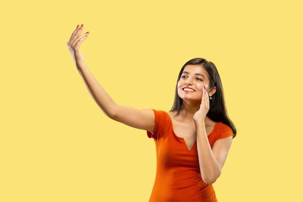 Portret van mooie vrouw geïsoleerd op gele studio achtergrond