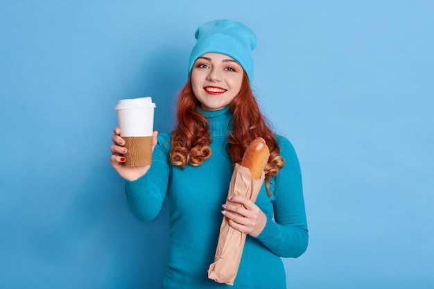 Portret van mooie vrouw, gekleed in casual trui en pet, oprecht glimlachend