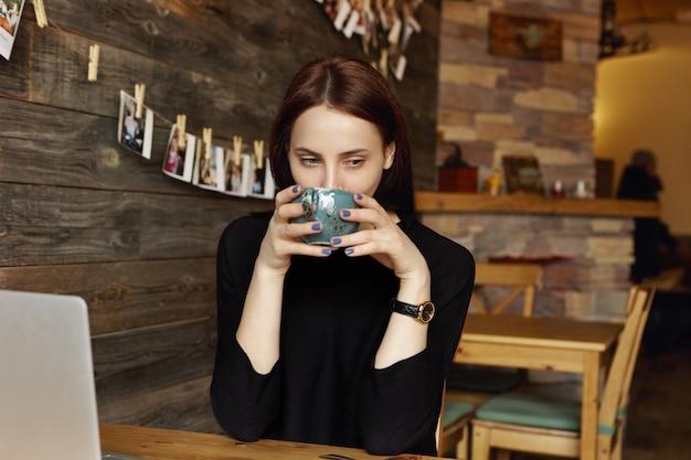 Portret van mooie vrouw, gekleed in zwarte jurk en polshorloge, genietend van de geur van verse cappuccino, met een grote mok op haar gezicht terwijl ze luncht in een gezellig café dat op internet surft op laptopcomputer