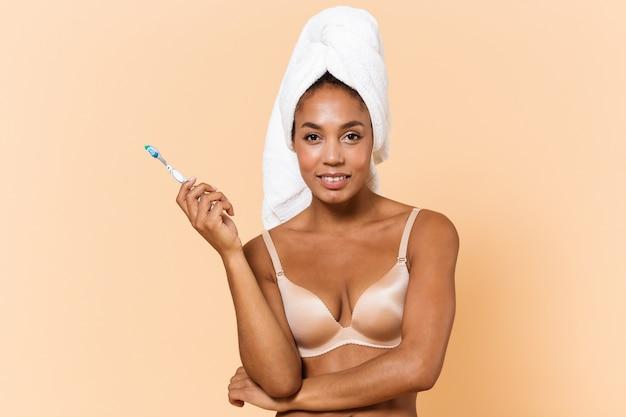 Portret van mooie vrouw gewikkeld in een handdoek en het dragen van witte lingerie met tandenborstel, terwijl staande geïsoleerd over beige muur