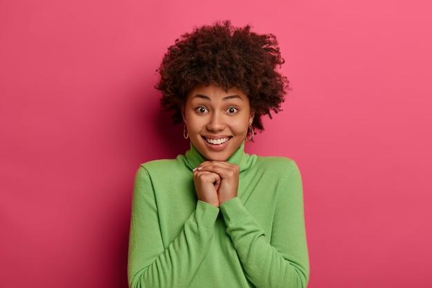 Portret van mooie vrouw heeft krullend kapsel, kijkt graag naar de camera, houdt handen onder de kin, draagt casual groene poloneck, heeft schattige glimlach, witte tanden