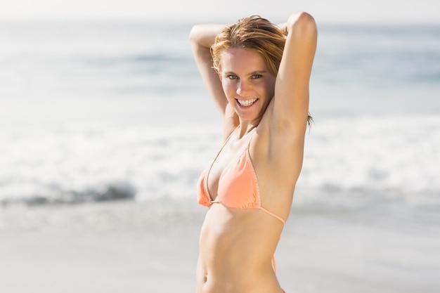 Portret van mooie vrouw in bikini die zich op het strand bevindt