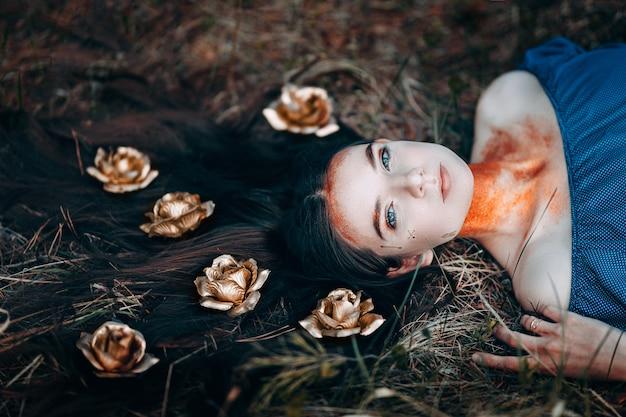 Portret van mooie vrouw in blauwe jurk, met een kroon van gouden rozen fee bos