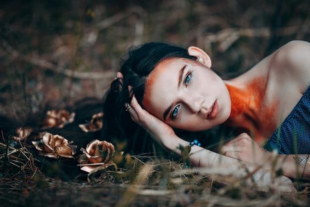 Portret van mooie vrouw in blauwe jurk, met gouden rozen fee bos