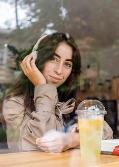 Portret van mooie vrouw in café met verse limonade en koptelefoon