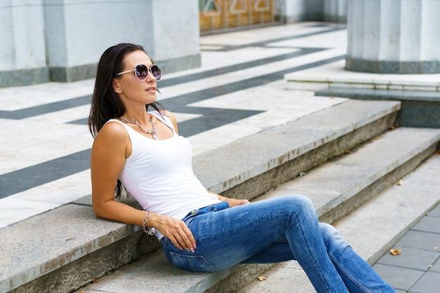 Portret van mooie vrouw in casual kleding en zonnebril zittend op trappen in de stad stijlvol en...