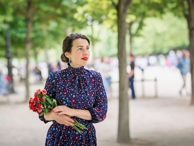 Portret van mooie vrouw in een donkerblauwe jurk genieten van een wandeling in het park