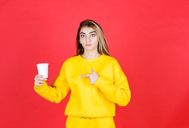 Portret van mooie vrouw in gele outfit poseren met kopje thee