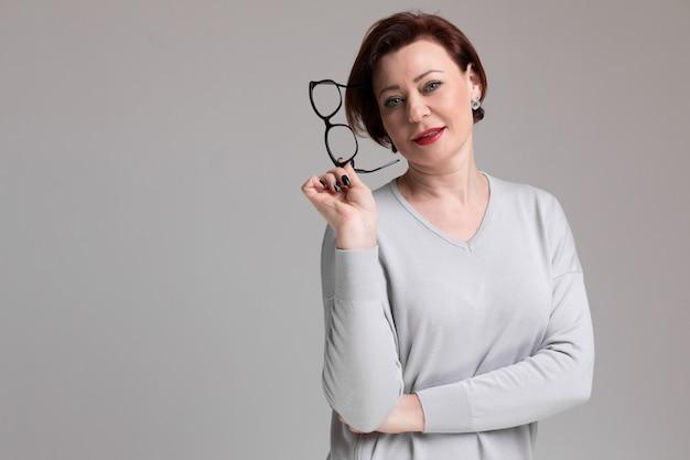 Portret van mooie vrouw in lichte kleding met glazen in hand op licht