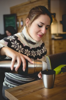 Portret van mooie vrouw in trui die koffie uit thermos in cup giet