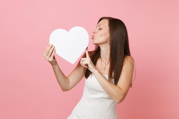 Portret van mooie vrouw in witte jurk die lippen blaast, stuur luchtkus naar wit hart met kopieerruimte in handen