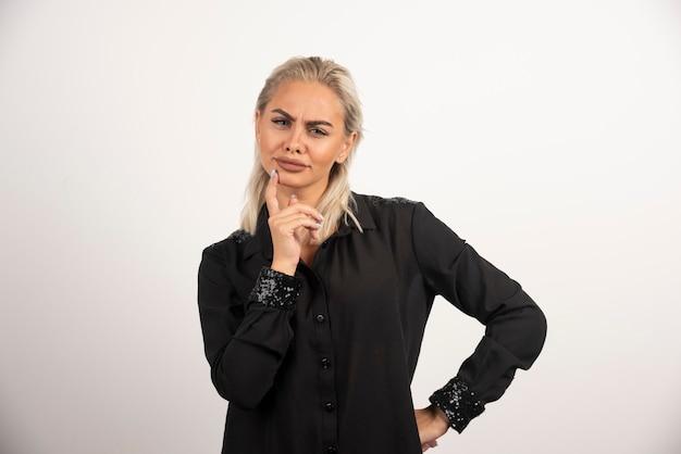 Portret van mooie vrouw in zwart shirt poseren op witte achtergrond. hoge kwaliteit foto