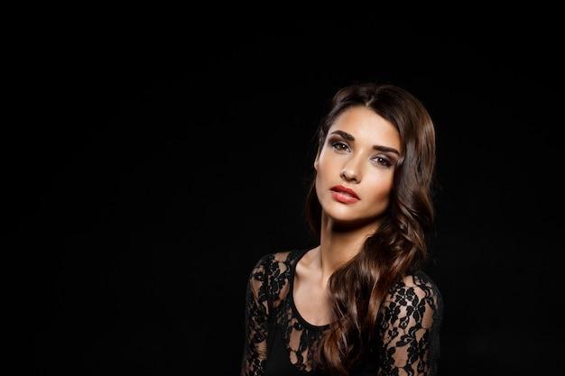 Portret van mooie vrouw in zwarte jurk over donkere muur