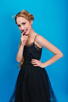 Portret van mooie vrouw, jonge dame die zich voordeed op feestje, vinger bijten. een mooie zwarte jurk dragen, een hoofdband van een kattenoor in diamanten, gouden manicure.