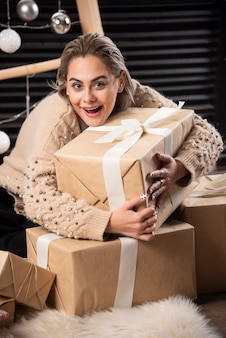 Portret van mooie vrouw knuffelen een doos met kerstcadeautjes