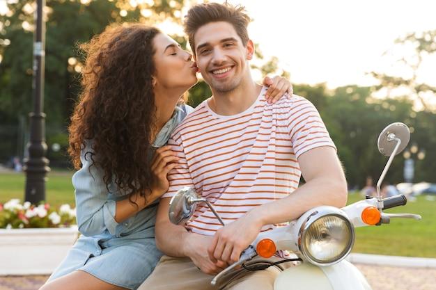 Portret van mooie vrouw kussen blanke man op de wang, zittend op de motor in stadspark
