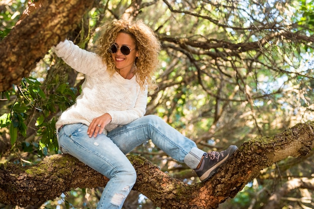 Portret van mooie vrouw lacht en speelt graag met een boom