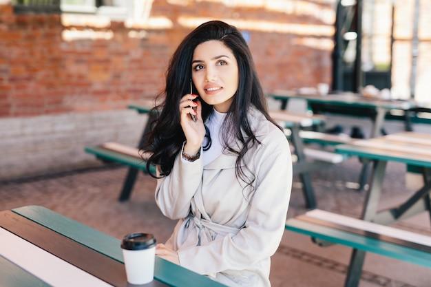 Portret van mooie vrouw met aantrekkelijke verschijning die witte formele kleding draagt die over mobiele telefoon spreekt en meeneemkoffie drinkt