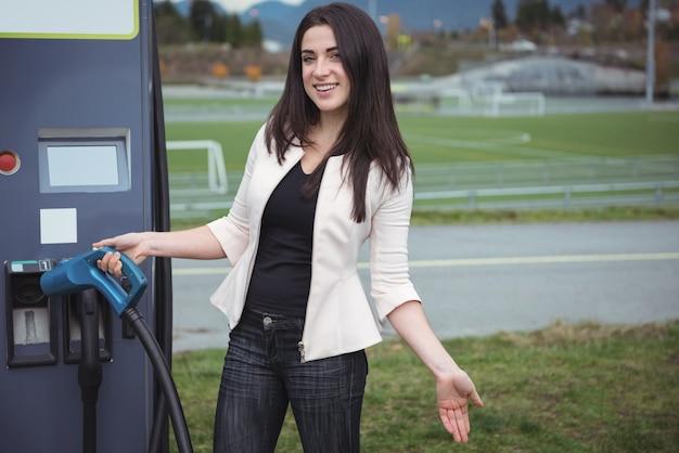 Portret van mooie vrouw met behulp van plug-in elektrische machine
