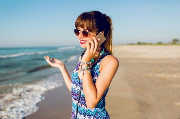 Portret van mooie vrouw met behulp van slimme telefoon op zonnig strand