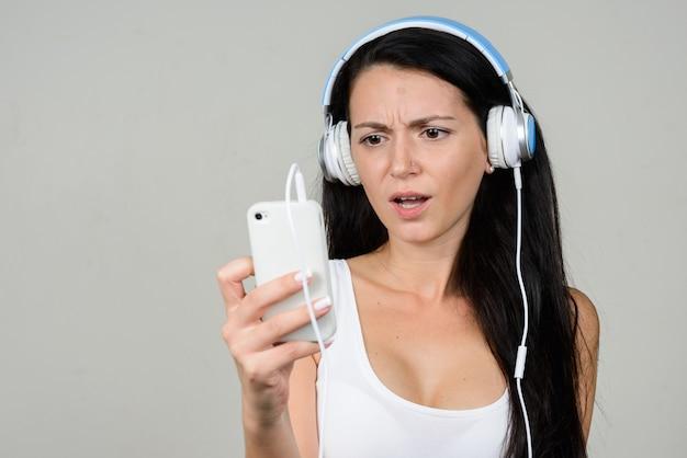 Portret van mooie vrouw met behulp van telefoon en luisteren naar muziek