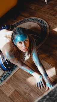 Portret van mooie vrouw met blauwe fonkelingen op haar gezicht. het concept van freaks en aliens. mensen zijn anders dan anderen. individualiteit
