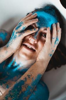 Portret van mooie vrouw met blauwe fonkelingen op haar gezicht in het bad. het concept van individualiteit
