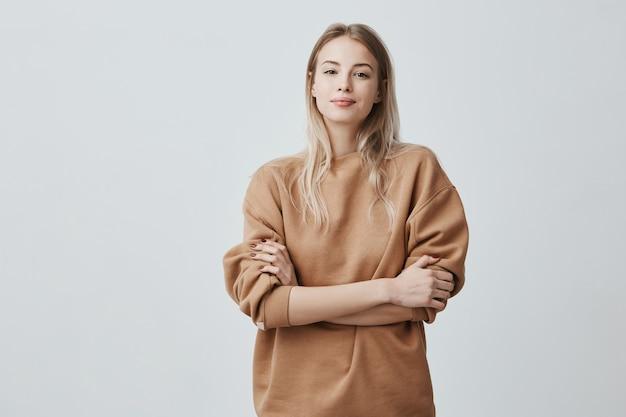 Portret van mooie vrouw met blond steil haar vrolijk lachend terwijl ze luistert naar complimenten, losse trui met lange mouwen dragen, armen over elkaar houden.