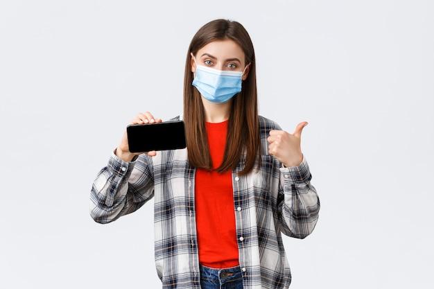 Portret van mooie vrouw met gezichtsmasker en mobiele telefoon