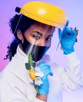 Portret van mooie vrouw met gezichtsschild en bloemenhandschoenen
