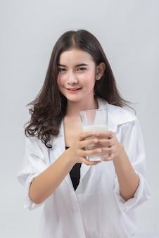 Portret van mooie vrouw met glas melk op grijs