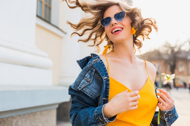Portret van mooie vrouw met haar glimlachen, stijlvolle kleding, spijkerjasje en gele top, modetrend, zomerstijl, gelukkige positieve stemming, zonnige dag, zonsopgang, emotioneel, vrolijk
